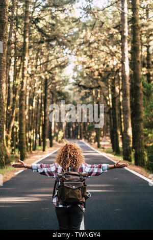Alternative travel concept with curly hipster woman viewed from back open his arms and feel the freedom of the outdoors nature standing in the middle - Stock Image