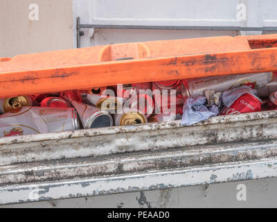 Stacks of dead beers cans in overflowing commercial recyling bin. - Stock Image