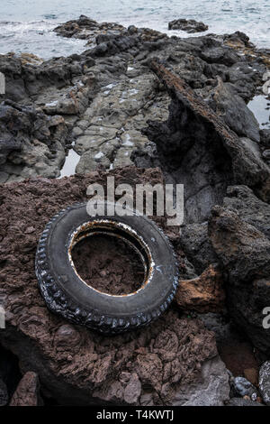 Old truck tyre washed up on the rocks at Playa San Juan, Tenerife, Canary Islands, Spain - Stock Image