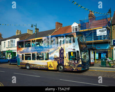 A double decker Midddlsbrough to Whitby bus at Guisborough North Yorkshire the bus covered in promotional images of Tourist Attractions in Whitby - Stock Image