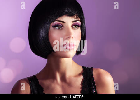 Fashion portrait of a beautiful woman over purple background, attractive model with gorgeous bob haircut and bright - Stock Image