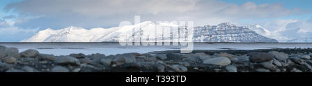 Panoramic landscape along the southern coast of Iceland with snow-covered mountains - Stock Image