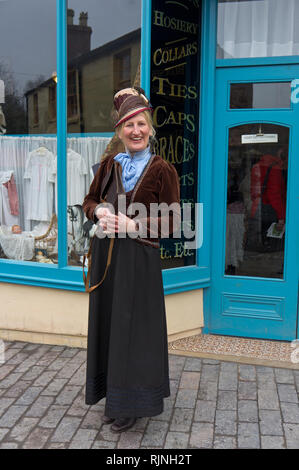Smiling lady volunteer, in stylish Victorian costume, outside a draper's store, Blists Hill Victorian Town, Shropshire, UK - Stock Image