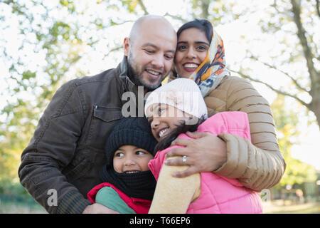 Portrait happy Muslim family hugging in autumn park - Stock Image