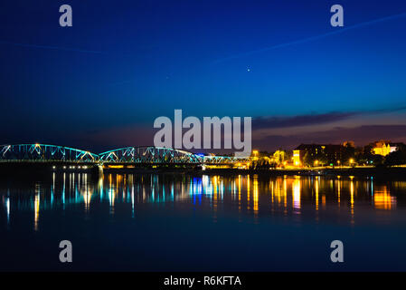 Panorama of night city from the bank of the river with illumination and star sky - Stock Image