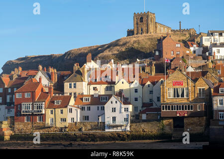 Winter sunlight on St Mary's Church and the red pantile roofs of  the Old Town Quarter, Whitby, North Yorkshire, UK - Stock Image