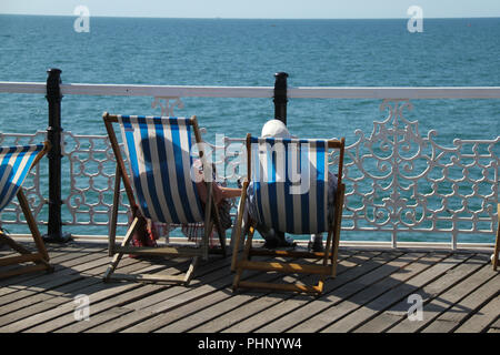Brighton, UK - September 1 2018: People bask in the sun on the Brighton Palace Pier on a sunny afternoon on 1​ September 2018.   The Pier, in the central waterfront section, opened in 1899 houses amusement rides as well as food kiosks.Credit: David Mbiyu /Alamy Live News - Stock Image