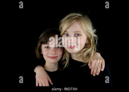 Two happy girls putting their arms around each other against a black background - Stock Image