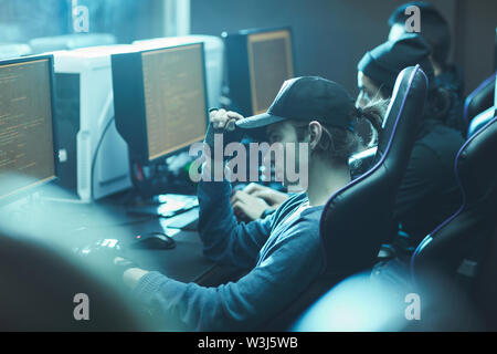 Young talented programmers in hipster outfits sitting at table and using powerful computers while coding app - Stock Image