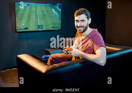 Portrait of a happy man with joy stick playing football game with gaming console sitting on the couch at the playing club - Stock Image