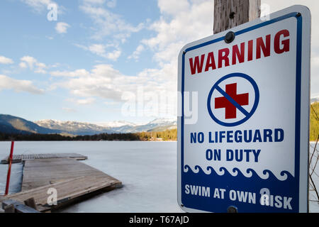 Sign warning that there is no lifeguard on duty at near a frozen winter lake. - Stock Image