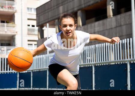 Teen girl playing basketball in an urban court - Stock Image