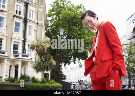 Chic woman in red suit in Notting Hill street, horizontal - Stock Image