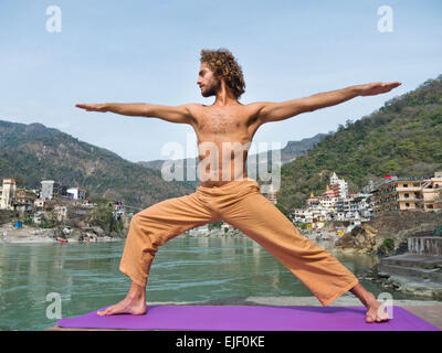 A man practicing yoga warrior pose by the Ganges river in Rishikesh India - Stock Image