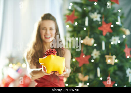 Closeup on yellow piggy bank trendy in hands of woman in red dress near Christmas tree in a hand of woman - Stock Image