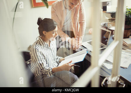 Business people reviewing paperwork at desk in office - Stock Image