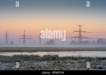 High voltage electrical pole. Electric powerline in the nature. Morning fog under the sunrise sky. - Stock Image