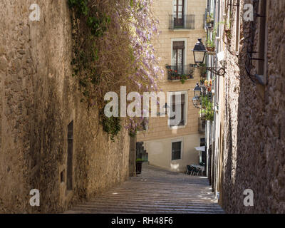 Steep Street down to a Cafe: Typical of the back streets in old Girona are the steep streets lined with old and some modern buldings - Stock Image