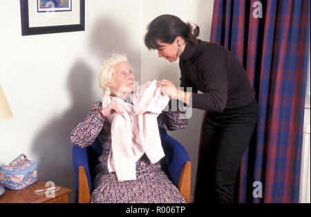 carer helping old lady to dress - Stock Image