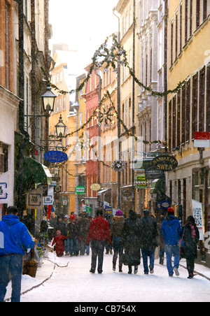 Snow falling on Christmas shopping people on Västerlånggatan in the Old town, (gamla stan) Stockholm, - Stock Image