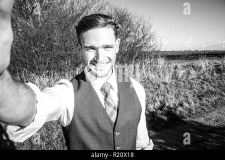 Good looking man taking selfie in countryside with trees and fields in background - Stock Image