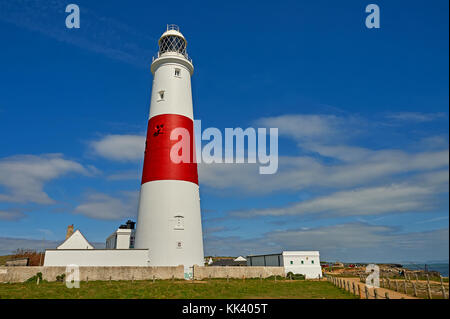 Portland Bill lighthouse in Dorset is a stereotypical white tower with wide red banding, seen against a blue sky. - Stock Image