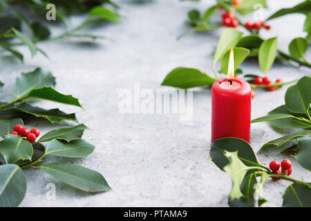 Christmas decorations, candle with evergreen decorations. Holly leaves with red berries. - Stock Image