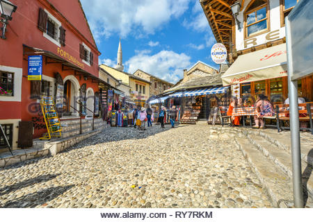A small market, shops, stores and a sidewalk cafe with tourists on a sunny day in old town Mostar, Bosnia and Herzegovina. - Stock Image