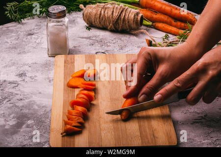 Kitchen background with cutting board carrot and salt shaker female hands cut carrot - Stock Image