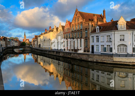 Pink clouds at dawn on the Belfry and historic buildings reflected in the typical canal, Bruges, West Flanders, Belgium, Europe - Stock Image