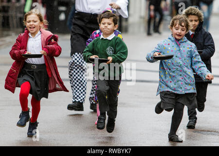 Chippenham, Wiltshire, UK. 5th March, 2019. Heavy rain this afternoon failed to dampen the spirits of local children who are pictured taking part in the annual pancake race on Chippenham high street.  Credit: Lynchpics/Alamy Live News - Stock Image