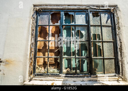 broken window on old building smashed glass panes derelict abandoned building - Stock Image