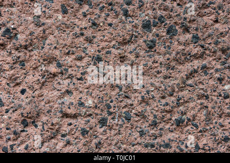 Brown stone or rock texture with black mineral inclusions. Wallpaper, pattern or background for a design project - Stock Image