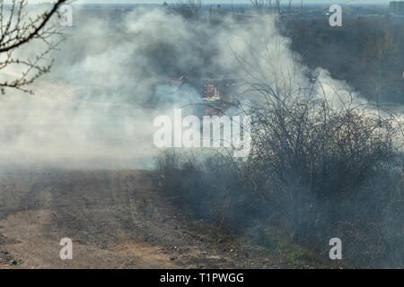 In early spring, fire spreads through dry vegetation, burning everything in its path. Heavy smoke and large fires harm agriculture and cause environme - Stock Image