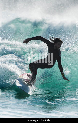 Dramatic surfing action as a surfer is silhouetted against the sunlight as rides a wave in a jade coloured sea at Fistral in Newquay in Cornwall. - Stock Image