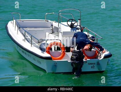 outboard boat engine being checked for faults by a boat engineer - Stock Image