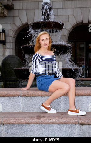 A young woman with long blond hair sitting beside a fountain on a breezy day at the City Square in Dundee, UK - Stock Image