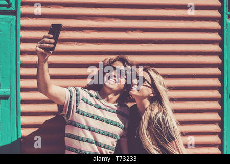 Millennial happy young caucasian couple of bou and girl taking selfie picture with coloured wall in background - people having fun with technology con - Stock Image