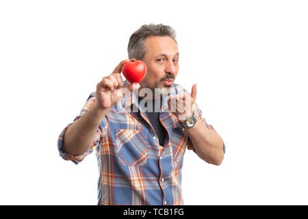 Friendly man holding red plastic heart and making send kisses gesture with hand near mouth as love concept isolated on white - Stock Image