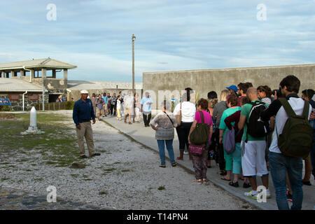 Tourists listen to a former prisoner, now a tour guide, in the prison yard at Robben Island, where Nelson Mandela was imprisoned during apartheid, Cap - Stock Image