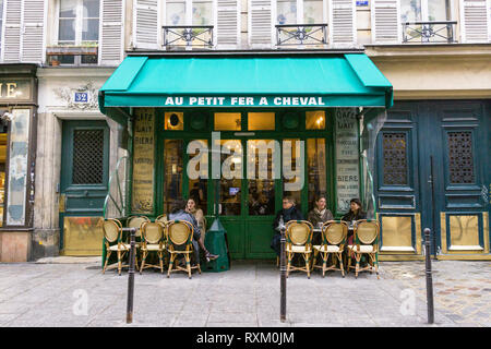 Patrons enjoying afternoon coffee at the cafe Au Petit Fer a Cheval in Marais district of Paris, France. - Stock Image