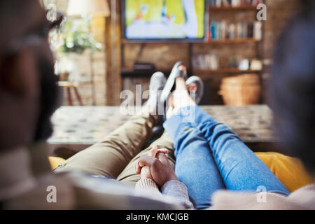 Affectionate couple holding hands, watching TV in living room - Stock Image