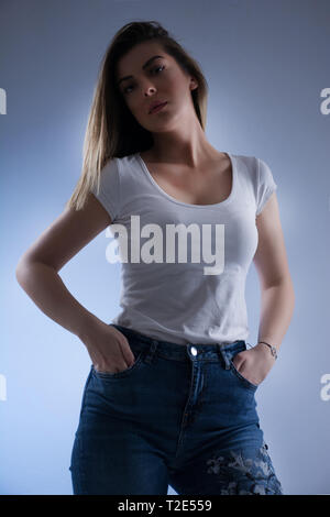 Low key girl portrait with blonde hair in white t shirt and blue jeans spreading hands, looking on camera and hands in pockets. Female portrait - Stock Image