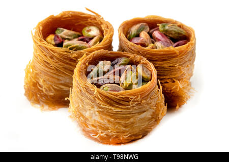 Bird nest baklava with pistachios on a white background - Stock Image