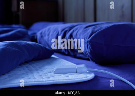 Electric heating blanket on a bed at night, thermotherapy for fibromyalgia syndrome and other rheumatic diseases - Stock Image
