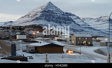 Snow Covered Houses By Mountains Against Sky At Night - Stock Image