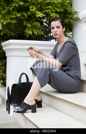Chic woman in jumpsuit sitting on doorstep in London street - Stock Image