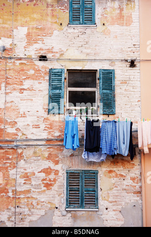 washing hangs from a colorful house in the historic Italian hilltown of Jesi - Stock Image