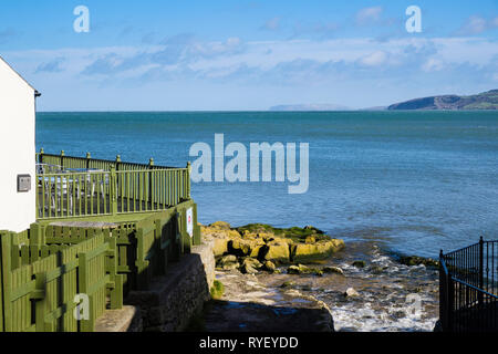 Bay Cafe and stream on rocky coast overlooking sea with Great Orme in distance. Benllech, Isle of Anglesey, North Wales, UK, Britain - Stock Image