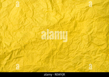 yellow crumpled paper texture as background. concept of school, abstract and stress - Stock Image
